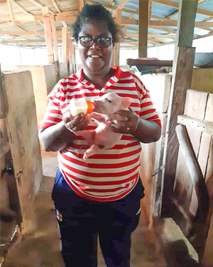 Catherine Adelegan SSL Feeding a Piglet At The Farm In Ewulu Nigeria